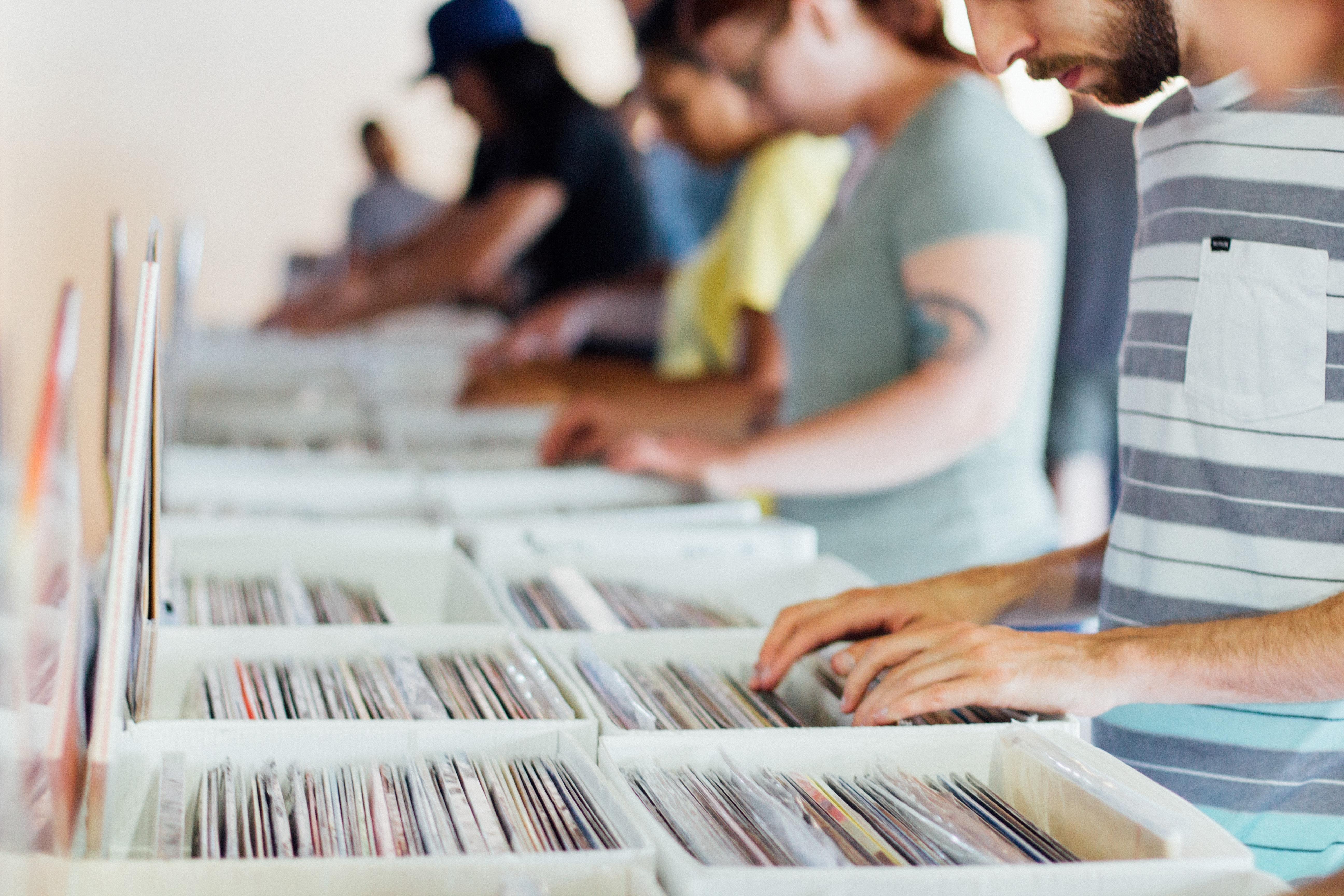 Plusieurs personnes effectuent leur recherche dans des bacs à disques